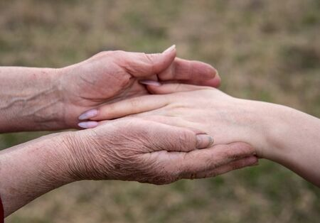 Photo pour The hand of a young girl in the elderly hands of her grandmother on a blurred background of nature. Conceptual family photo, continuity of generations. - image libre de droit