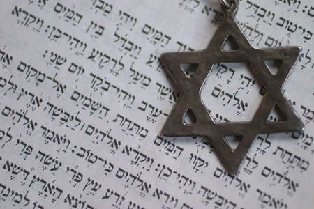 Star of David over the first page of the old testament in Hebrew. The word in the center of the star is