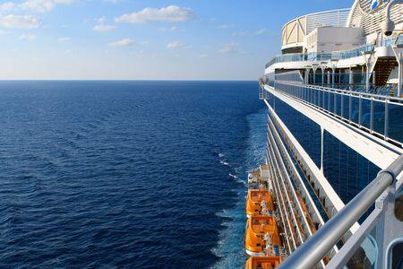 Foto de Blue Atlantic ocean and white clouds above the horizon in blue sky with cruise ship perspective and orange lifeboats. - Imagen libre de derechos