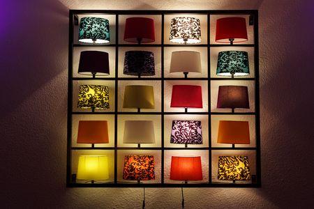 Various lamp on shelves near a wall