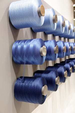 spools with threads hanging on the wall
