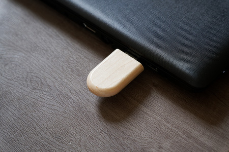 Usb flash drive with wooden surface on desk for USB port plug-in computer laptop for transfer data and backup business concept.