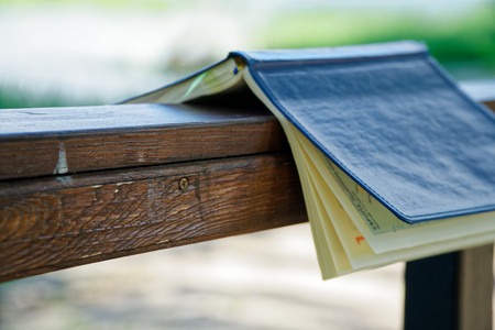 Wind turns the pages of open Notebook lies on wooden handrail in park, business concept.