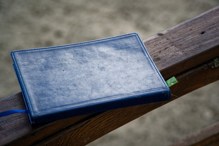 Blue Notebook lies on wooden handrail in park, business concept.