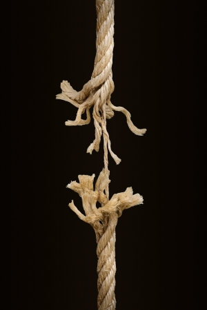 Close up of a breaking rope over a dark background