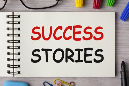 Success Stories written on notebook with marker pen and glasses on wooden desk. Business Concept.
