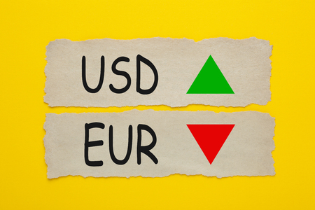 USD EUR symbol icon up down written on old torn paper on yellow background.