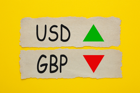 USD GBP symbol icon up down written on old torn paper on yellow background.