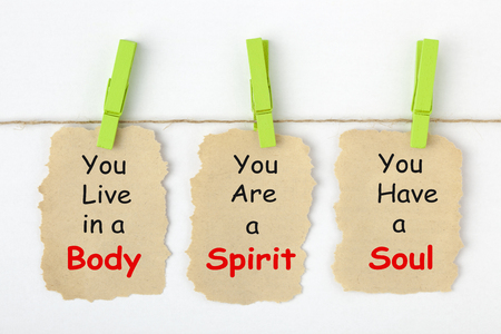 Body Spirit Soul written on old torn paper with clip hanging on white background.