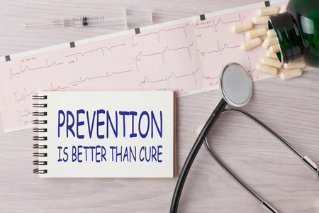 Prevention is Better than Cure written on notebook with stethoscope, syringe and pills. Medical concept.