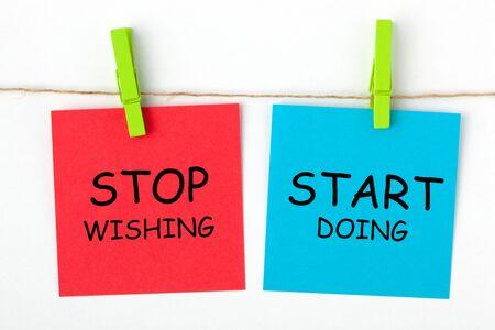 Foto de The phrase Stop Wishing Start Doing written on color notes with wooden pinch. - Imagen libre de derechos