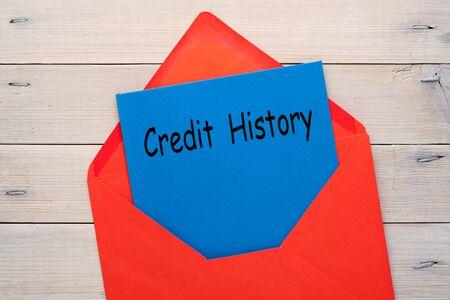 Photo pour Credit history document in red envelope on wooden background. Business concept - image libre de droit
