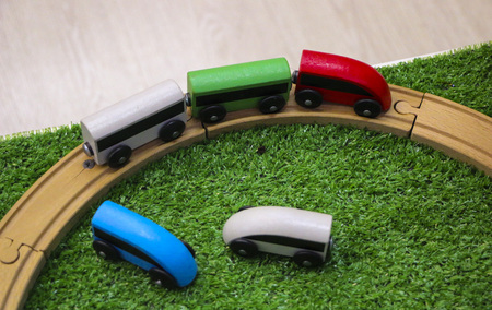 Photo pour Children's wooden train with cars, railway and wooden trees on artificial plastic green grass. - image libre de droit