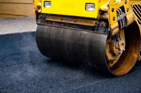 Foto de Compact steamroller flatten out the asphalt. - Imagen libre de derechos