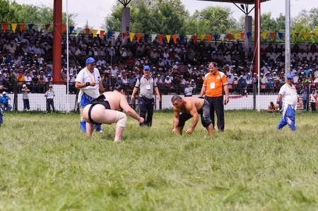 EDIRNE, TURKEY - JULY 26, 2010: Wrestlers Turkish pehlivan and Japanese sumo wrestler at the competition in Kirkpinar. Kirkpinar is a Turkish oil-wrestling (Turkish: yagli gures) tournament.