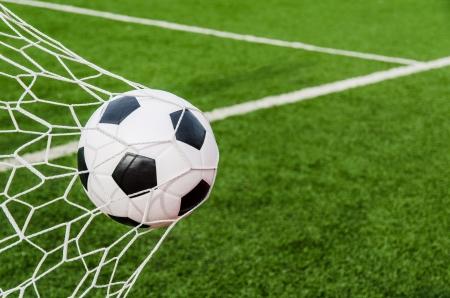 Soccer football in Goal net with green grass field