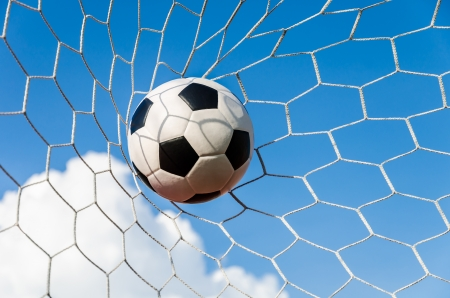 Soccer ball in Goal net with cloudy sky background