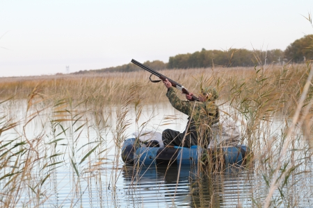 Hunter in an inflatable boat shoots duck