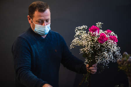 Foto de Happy caucasian florist making bouquets of red and pink roses for Valentine's day. Concept of human emotions, facial expression, love, and hard work in this pandemic times. - Imagen libre de derechos