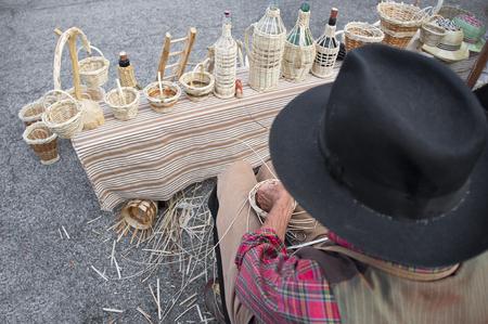 expert hands of the elderly craftsman creates a wicker basket