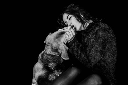 Photo pour girl who squeezes and kisses her dog with passion - image libre de droit