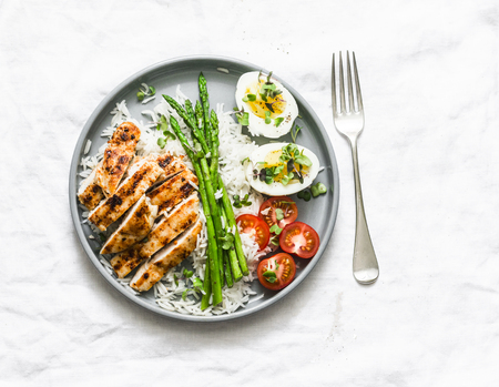 Photo for Balanced healthy lunch - rice, asparagus, grilled chicken, boiled egg on a light background, top view - Royalty Free Image
