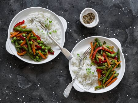 Photo for Green beans, sweet peppers, carrots, onions, green peas stir fry and rice on a dark background, top view. Fast diet vegetarian lunch - Royalty Free Image