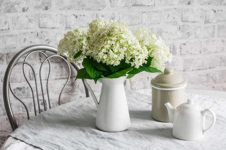 Photo pour Cozy kitchen in scandinavian style. Bouquet of hydrangeas, teapot, metal jar on the table in a bright room. Cozy home concept - image libre de droit