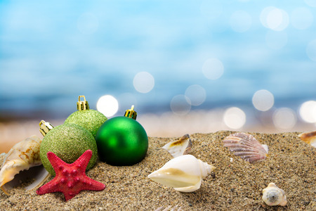 Christmas balls and shells on sand with summer sea background