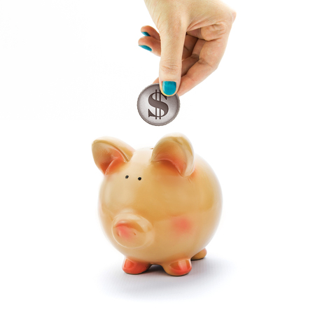 Photo pour Hand depositing coin with dollar sign in piggy bank - image libre de droit