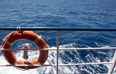 Seascape from boat with railing and  lifebuoy
