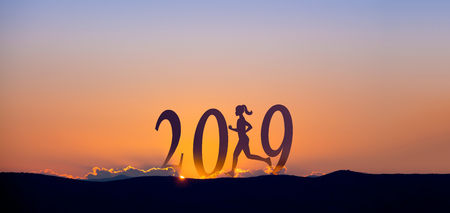 Foto de 2019 On dark mountains with silhouette of a woman running and sunrise as background. - Imagen libre de derechos