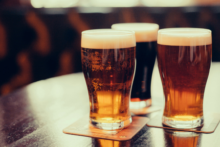 Photo for Glasses of light and dark beer on a pub background. - Royalty Free Image