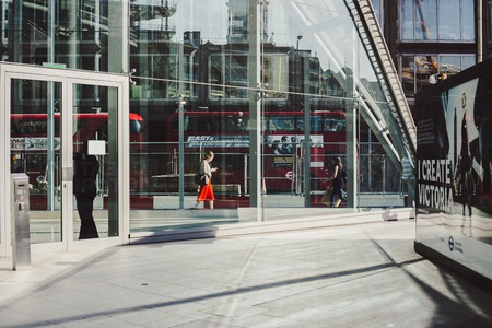 LONDON, UK - April 14, 2015: young business woman walking along the road with traffic and red buses on background.