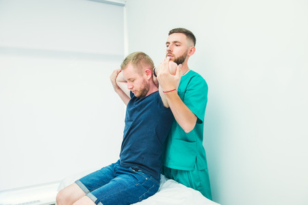 Male patient receiving massage from therapist. A chiropractor stretching his patient's spine and hands in medical office. Neurological physical examination. Osteopathy, chiropractic, physiotherapy