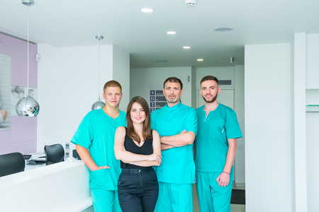 Smiling portrait team in uniform providing healthcare treatment in modern medical centre. Clinic, profession, people, health care and medicine concept - happy group of medics or doctors at hospital
