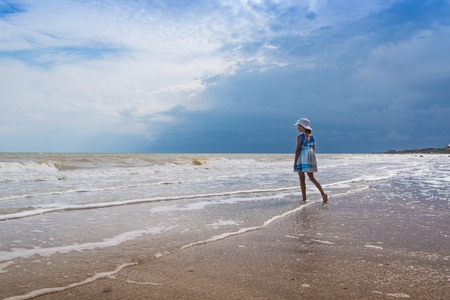 Photo pour Beautiful seascape. Girl in dress and white hat on the beach over blue sky background - image libre de droit