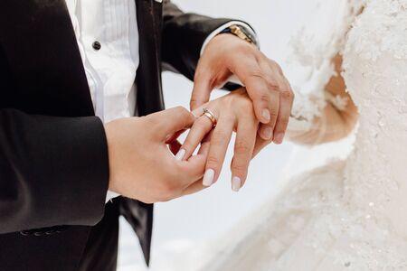 Photo pour Groom Putting Jewelry Golden Ring on Bride Finger - image libre de droit
