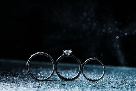 Photo pour three wedding rings dark background with copy space. Shiny water drops like fog - image libre de droit