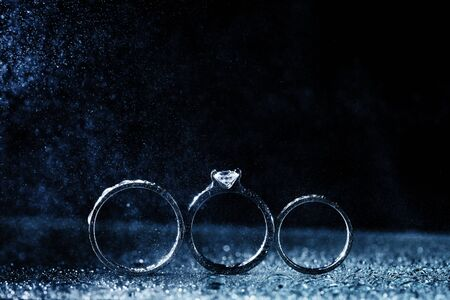 Photo pour three wedding rings dark background with copy space. Shiny water drops like fog. - image libre de droit