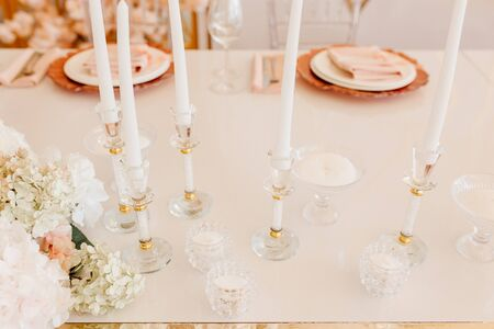 Foto für Candles Atanding in Crystal Decorative Candlsticks and Flower Bouquet on Dining Table Horizontal Photography. Napkin on Plates for Delicious Meal and Wine Glasses on Blurred Background - Lizenzfreies Bild