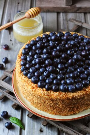 Homemade honey cake decorated with blueberry on a wooden background, top view