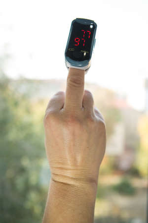 Photo pour Blood oxygen saturation is the most important indicator of health status in the context of the coronavirus pandemic. Human hand with a pulse oximeter on the finger. Hand gestures. - image libre de droit