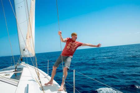 Photo pour A man on board a sailing yacht at sea. Yachting. Active lifestyle concept. - image libre de droit