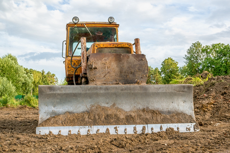 Photo for Old excavator working clearing land at sunset of a Sunny day. - Royalty Free Image
