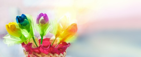 Foto de Delicate multicolored buds of tulips handmade from thin paper on a blurred  on a sunny day. - Imagen libre de derechos