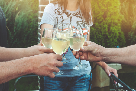 Photo pour Tinkling glasses of white wine and toast. Young people celebrate a birthday at a picnic. - image libre de droit