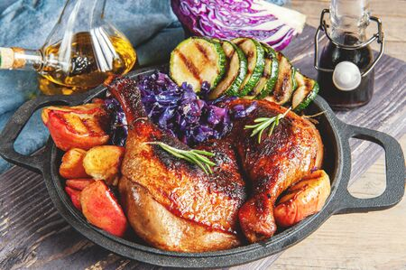 Photo pour Fried pickled duck legs with a side dish of vegetables . Grilled zucchini, red cabbage and spices on a wooden table. - image libre de droit