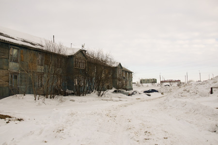 Old two-storied blue house in winter with snow outdoor. Poverty and misery, North