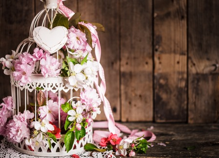 Bird cage with wooden heart with sakura and apple flowers. Wedding decorations with pink ribbon with copy space
